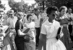 "One of the ""Little Rock Nine"" braves a jeering crowd."